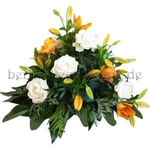 Hohes Trauergesteck aus weißen Edelrosen und orangefarbenen Lilien