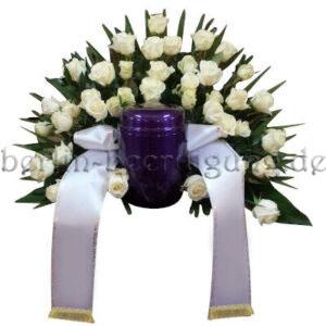 Weißes Urnenhintergesteck aus Rosen mit Trauerschleife