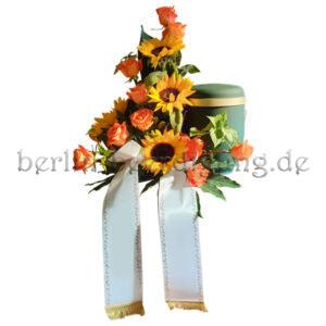 Freundliches Nebengesteck mit gelben Sonnenblumen orangenen Rosen und Schleife