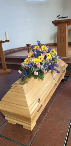 Sargbestattung mit Blumen