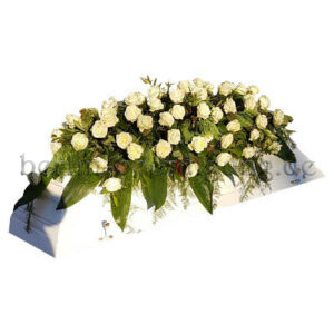 Große Sargdecke aus weißen Rosen auf Blattgrün