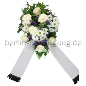 Weißes Trauergesteck mit blauen Akzenten und Schleifenbändern