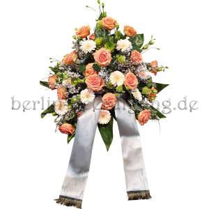 Freundliches hohes Blumengesteck mit Trauerschleife