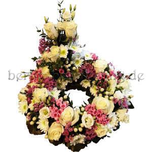 Blumenkranz mit erhöhtem Teilgesteck aus weißen Rosen, weißen Chrysanthemen, rosa Bouvardien, Lysianthus und Johanniskrautbeeren